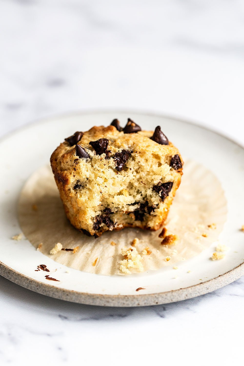 Chocolate chip muffin on a plate with a bite taken out with gooey chocolate inside