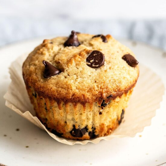 Chocolate chip muffin on a plate with the paper liner removed