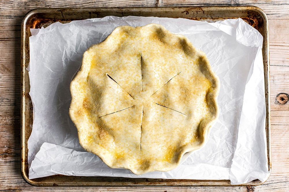 Unbaked apple pie covered with egg wash and sprinkled with coarse sugar