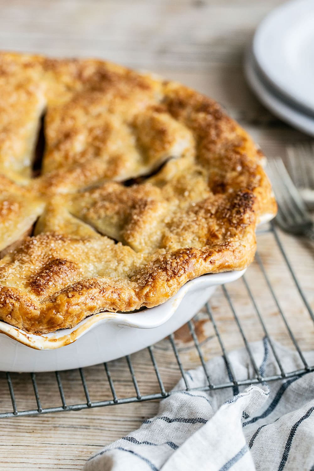 Double crust apple pie on a cooling rack on a wooden table