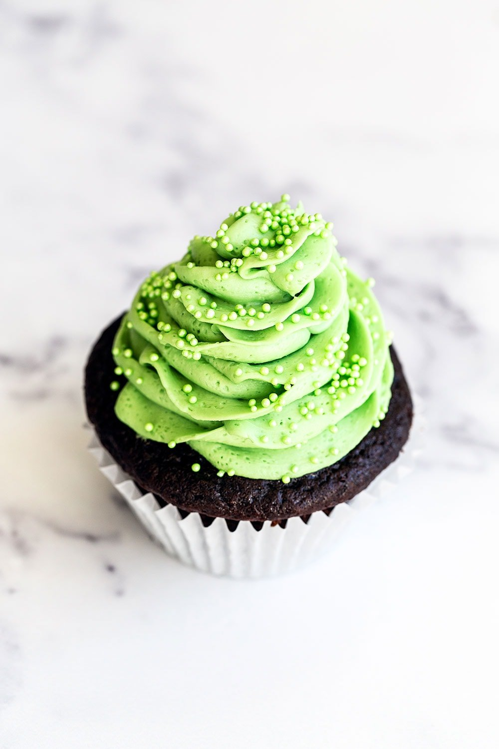 One chocolate mint cupcake on marble counter