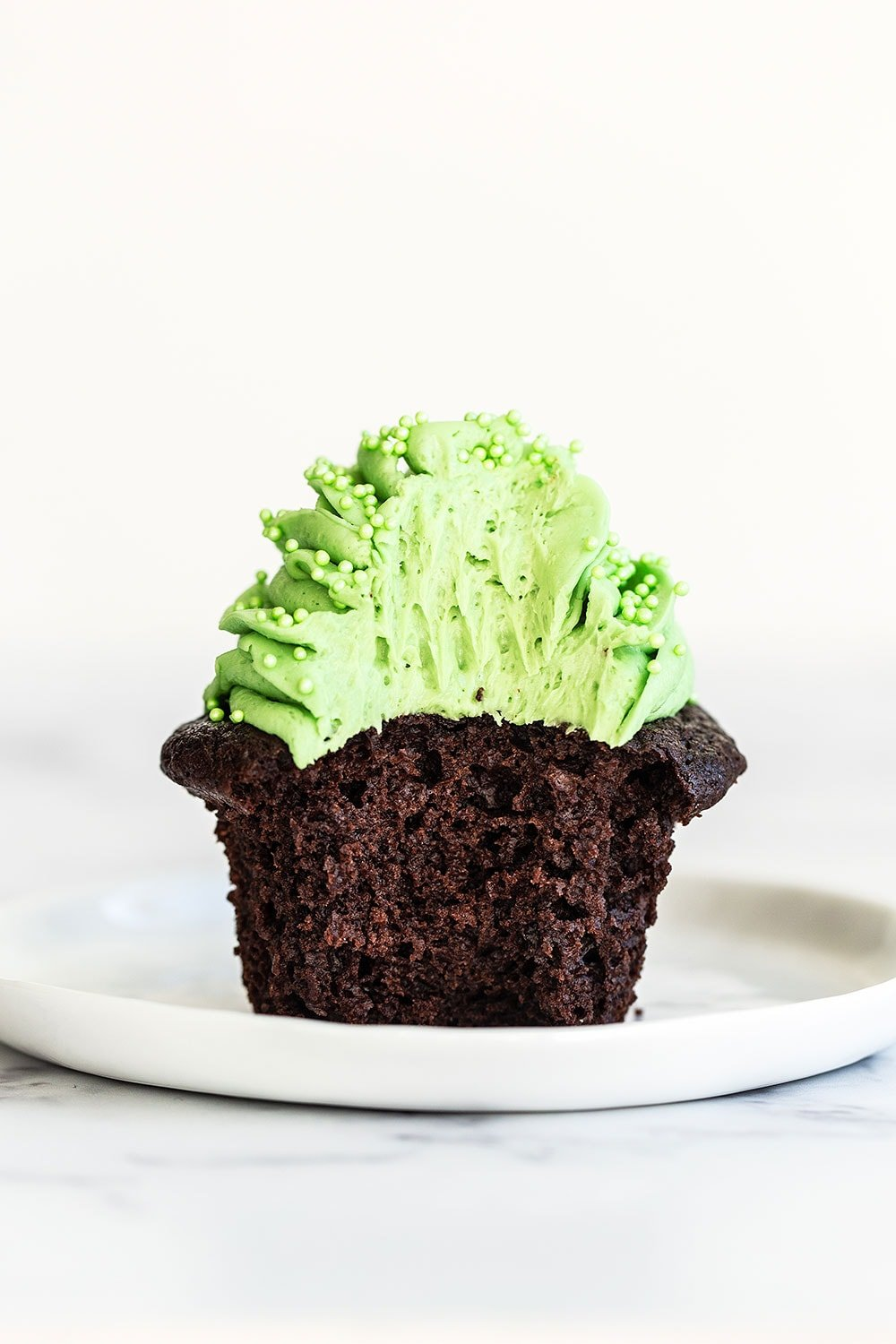 Chocolate mint cupcake on a plate with a bite taken out