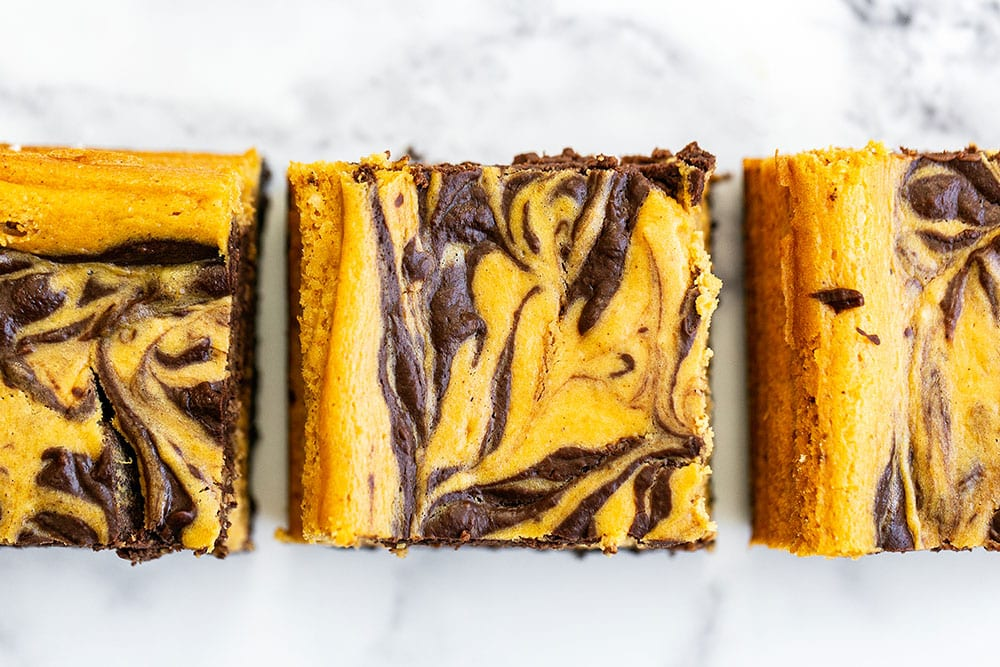 Pumpkin chocolate cheesecake cut into bars