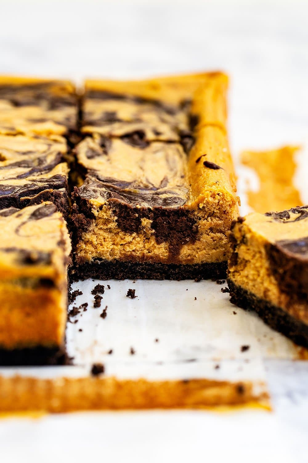 Pumpkin chocolate cheesecake being cut into squares