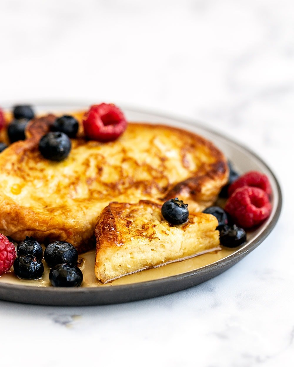 Bite of fluffy French toast made with Challah bread on a plate with syrup and fruit