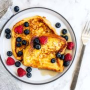 French toast with berries and maple syrup on a plate