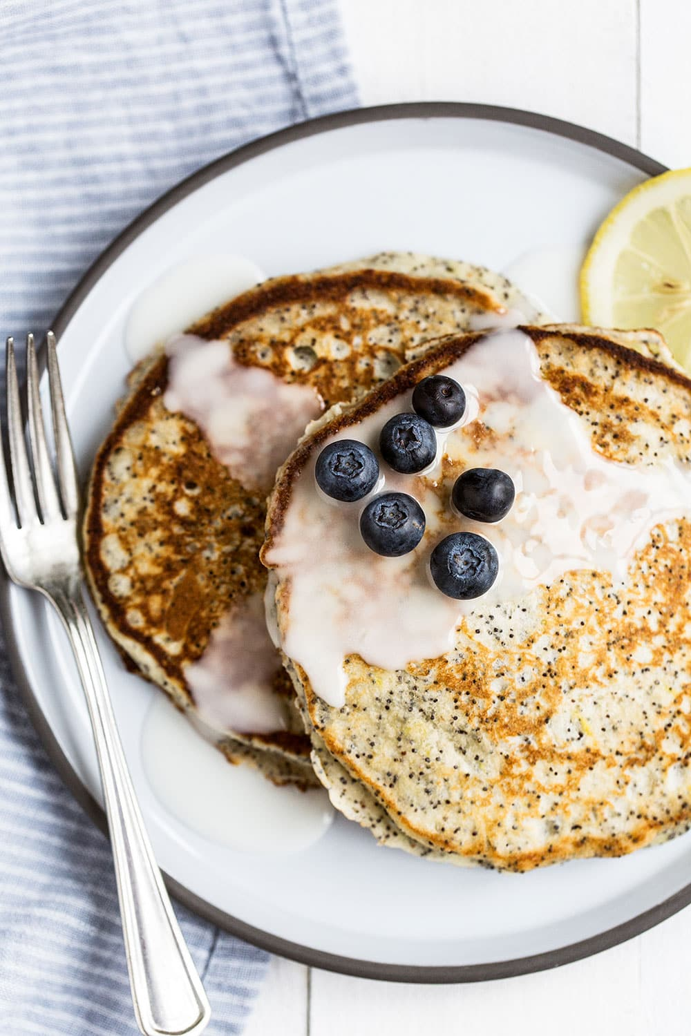 Lemon Poppy Seed pancakes with a sweet lemon glaze can be made ahead of time and are so flavorful and fluffy!