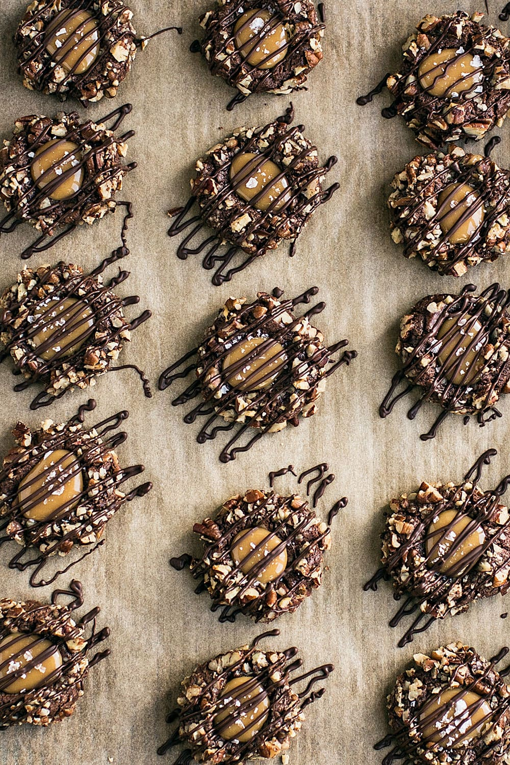 This Turtle Thumbprint Cookie recipe features a cocoa cookie rolled in pecans, filled with a salted caramel thumbprint, and drizzled with chocolate. A perfect Christmas cookie recipe!