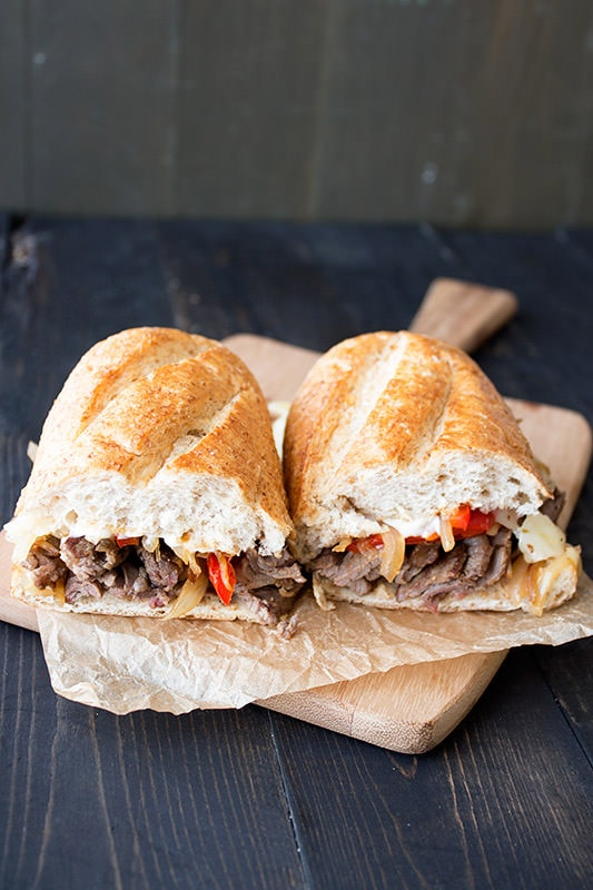 Homemade cheesesteaks are stuffed with sliced steak, peppers, onions ...
