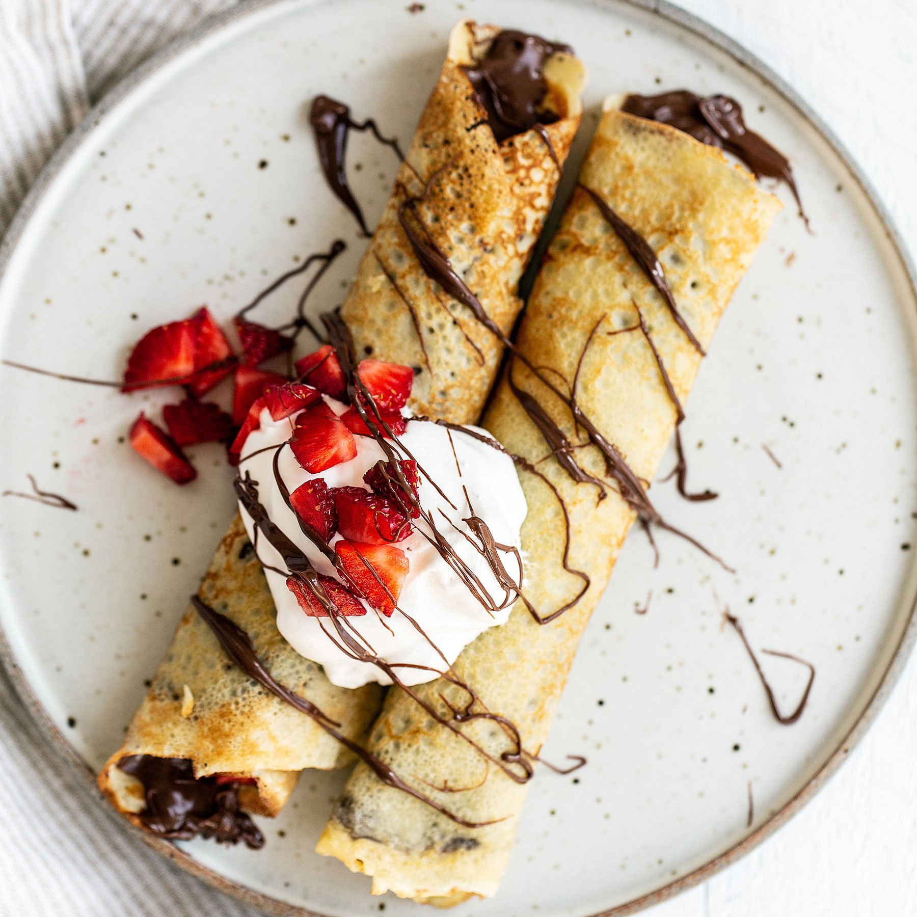 Two crepes on a plate with nutella, strawberries, and whipped cream on top