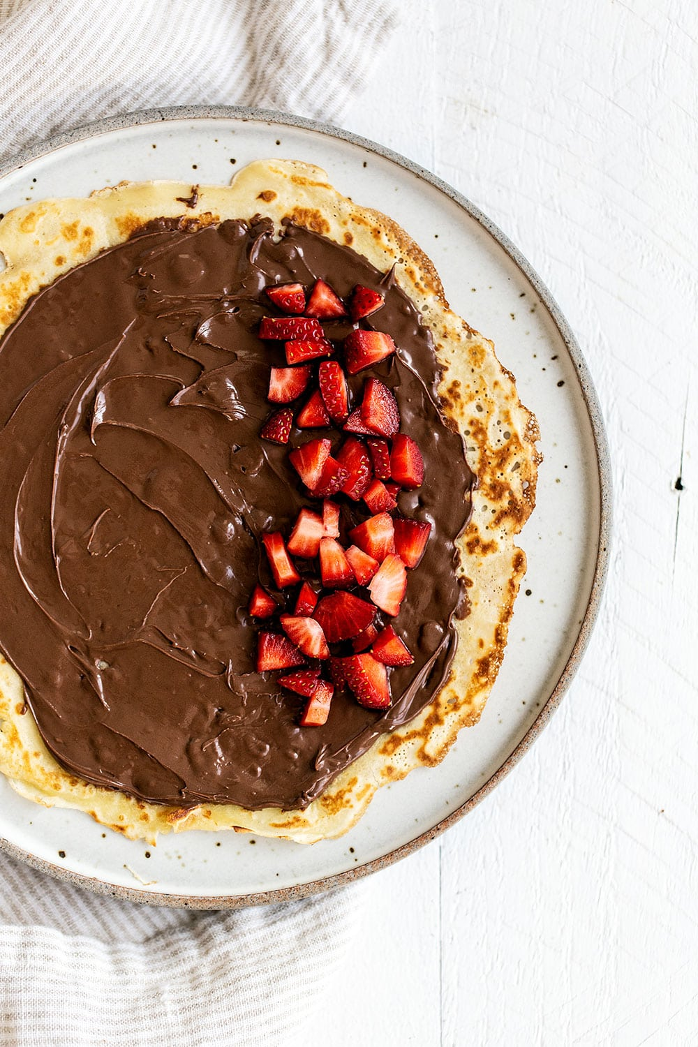 Open crepe on a plate with a generous spread of nutella and chopped strawberries