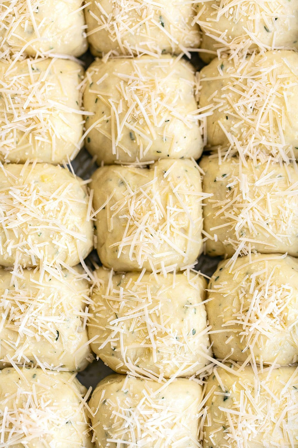 Garlic herb and cheese dinner rolls ready to be baked