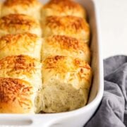 Garlic herb and cheese dinner rolls in a ceramic rectangular baking dish with one removed