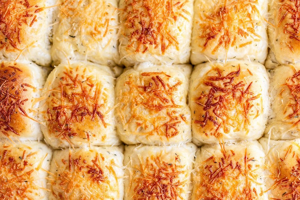 Garlic herb and cheese bread rolls in the baking dish golden brown and ready to eat
