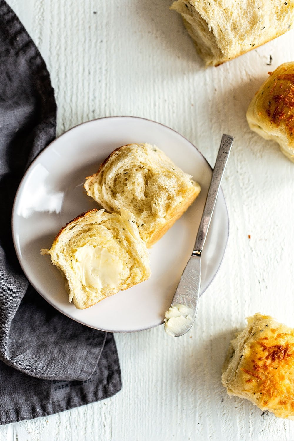Soft and fluffy garlic herb and cheese bread roll cut in half on a plate with butter