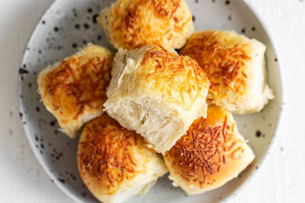 Garlic herb and cheese dinner rolls stacked on a plate