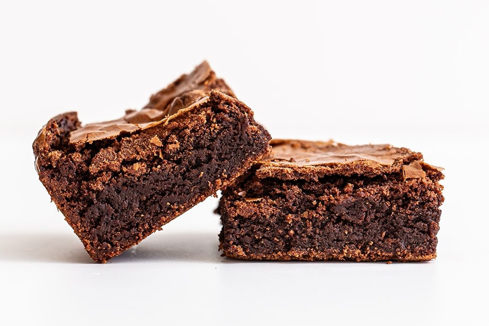 stack of fudgy ultimate brownies leaning on each other