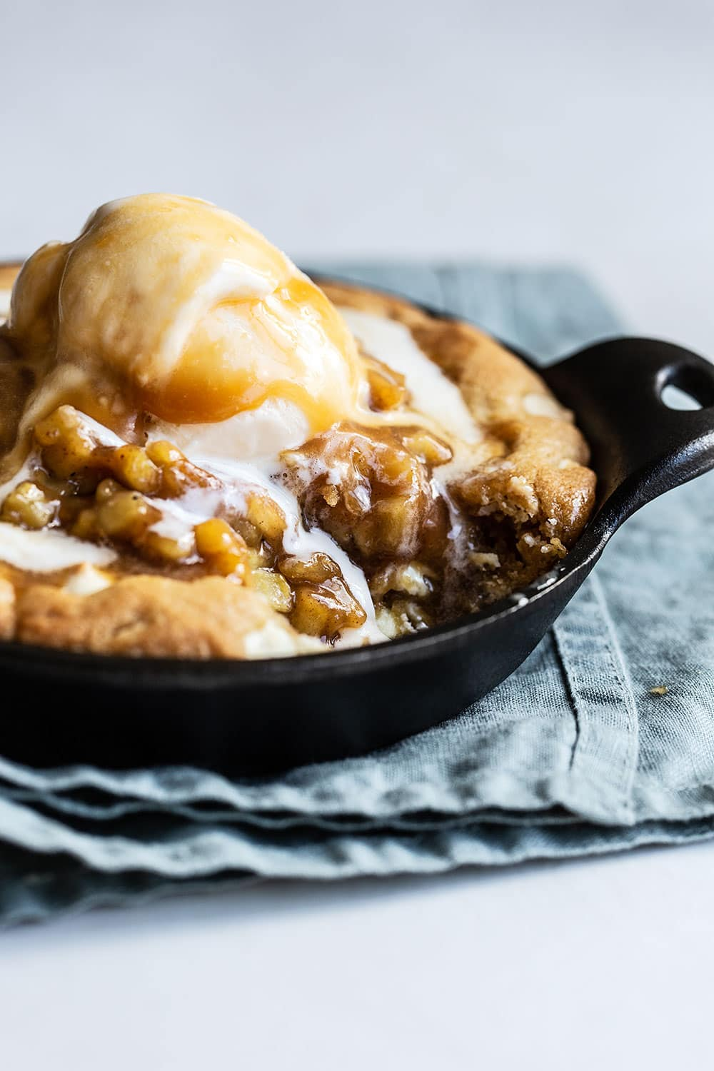 A bite taken out of gooey white chocolate pizookie topped with apple pie filling, caramel, and ice cream
