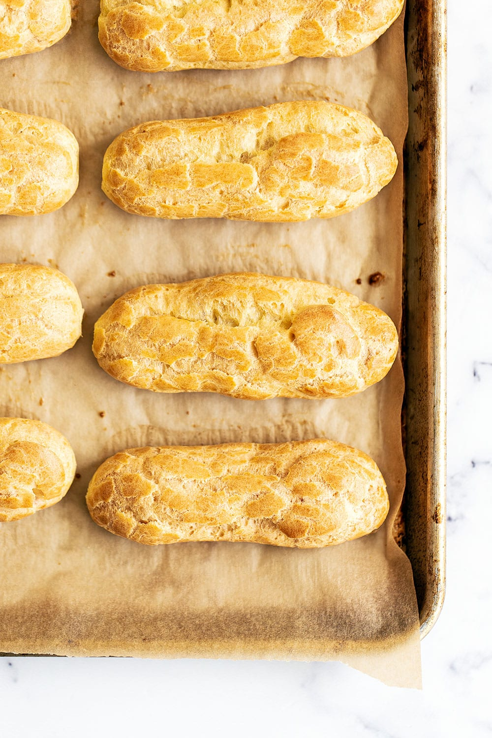 Unglazed and unfilled eclairs on a baking tray