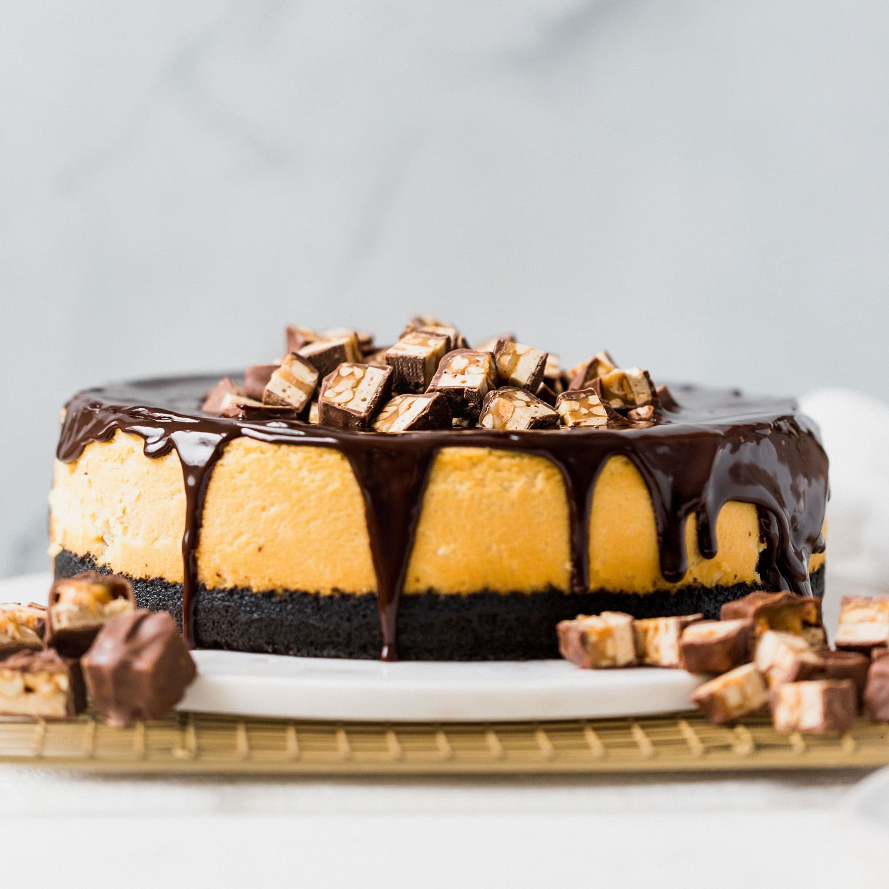 Decadent Snickers Cheesecake recipe with Oreo crust and chocolate ganache!
