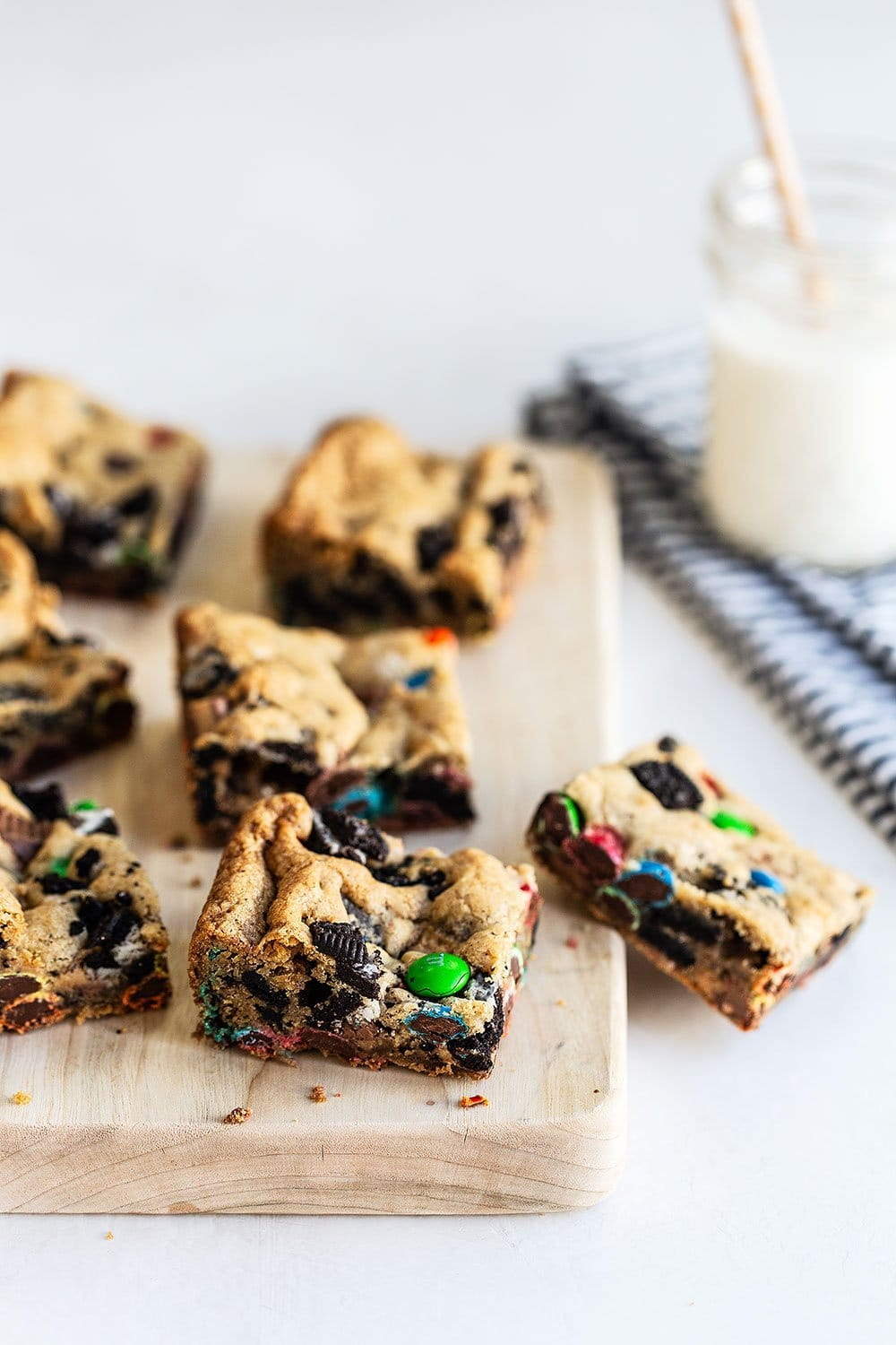 Loaded cookie bar squares on a cutting board with a glass of milk