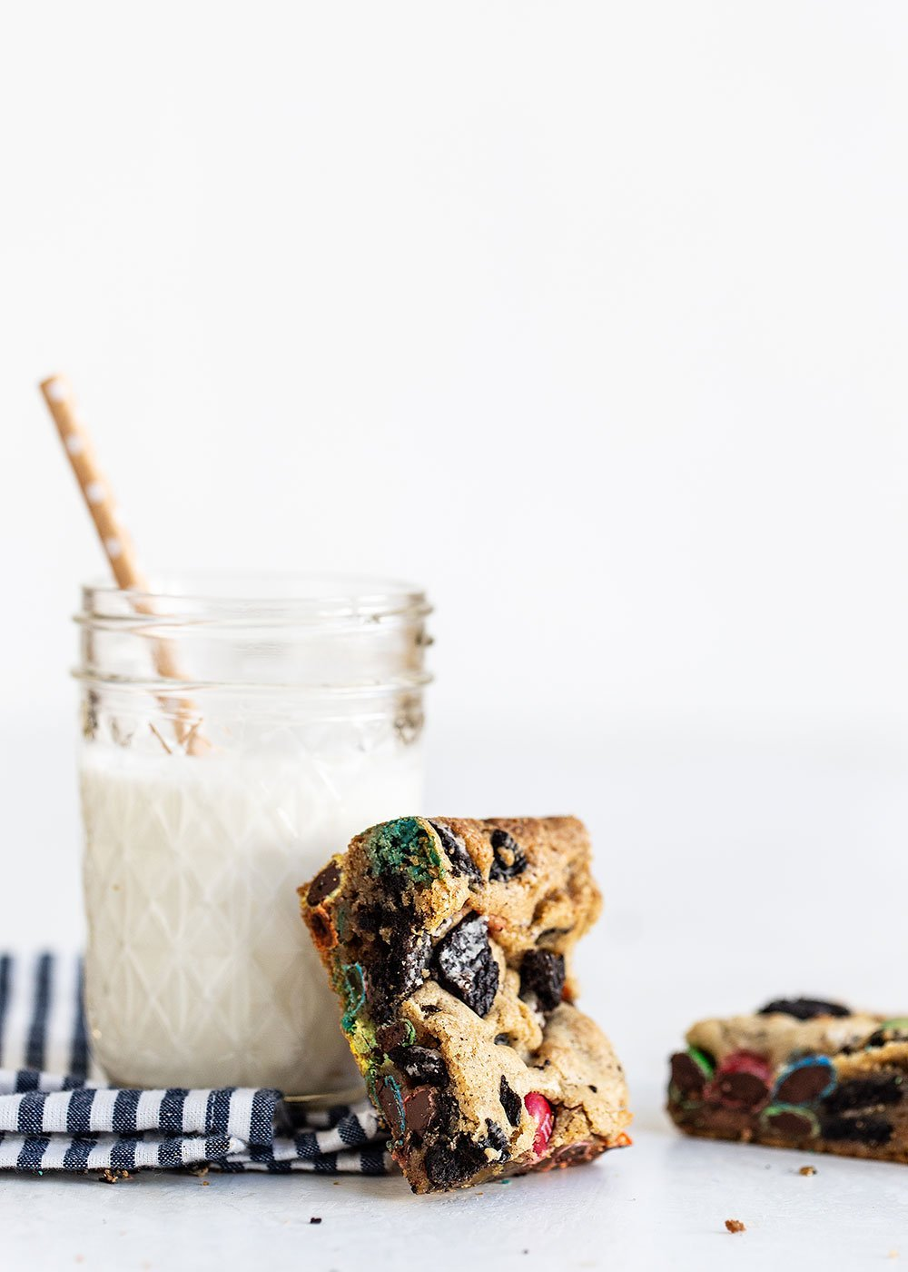 Loaded cookie bar leaning against glass of milk with a straw