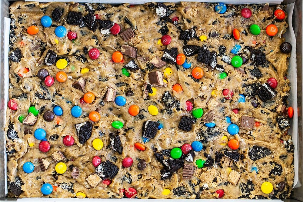 Loaded cookie dough pressed into baking pan with chopped Oreos, M&Ms, and Reese's