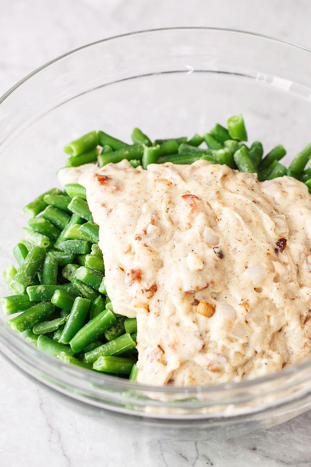 Fresh green beans and gravy mixture in a bowl for cheesy green bean casserole