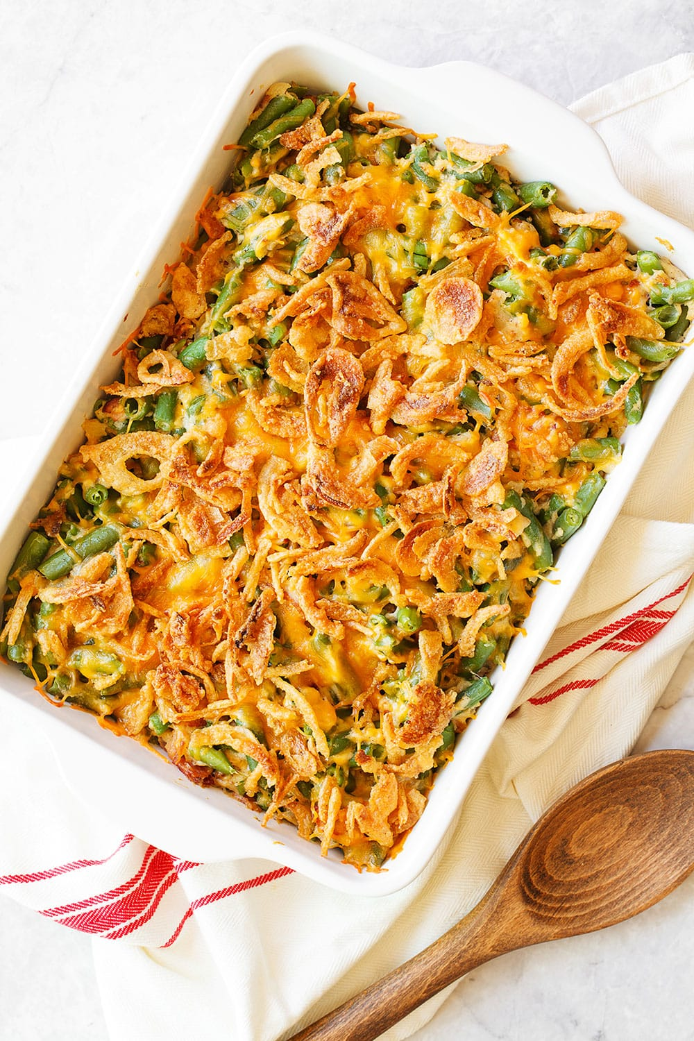 Cheesy Green Bean Casserole with Bacon is bursting with so many mouthwatering savory flavors, you'll never want make regular green bean casserole again! Best of all, there's no canned condensed soup!