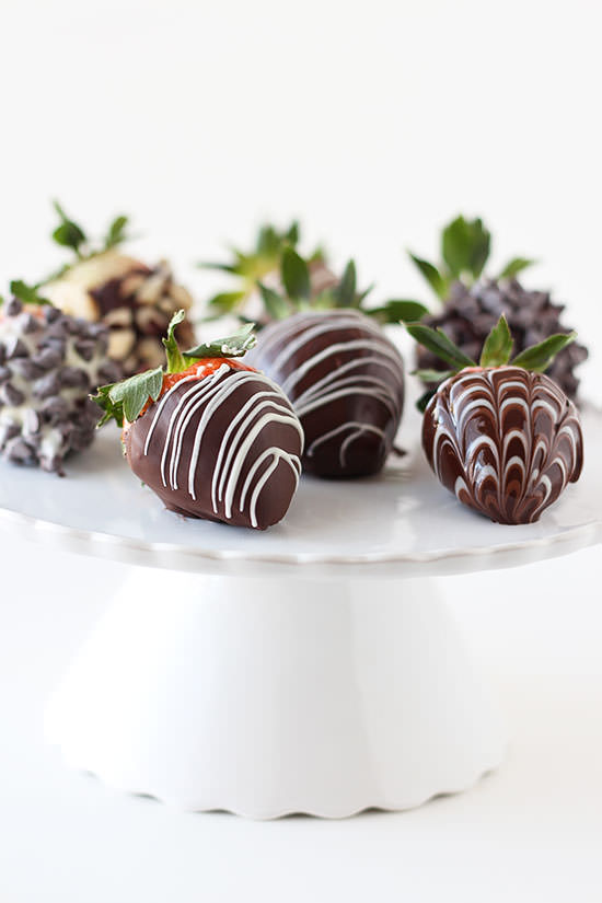 Pedestal of chocolate dipped strawberries with white chocolate drizzle