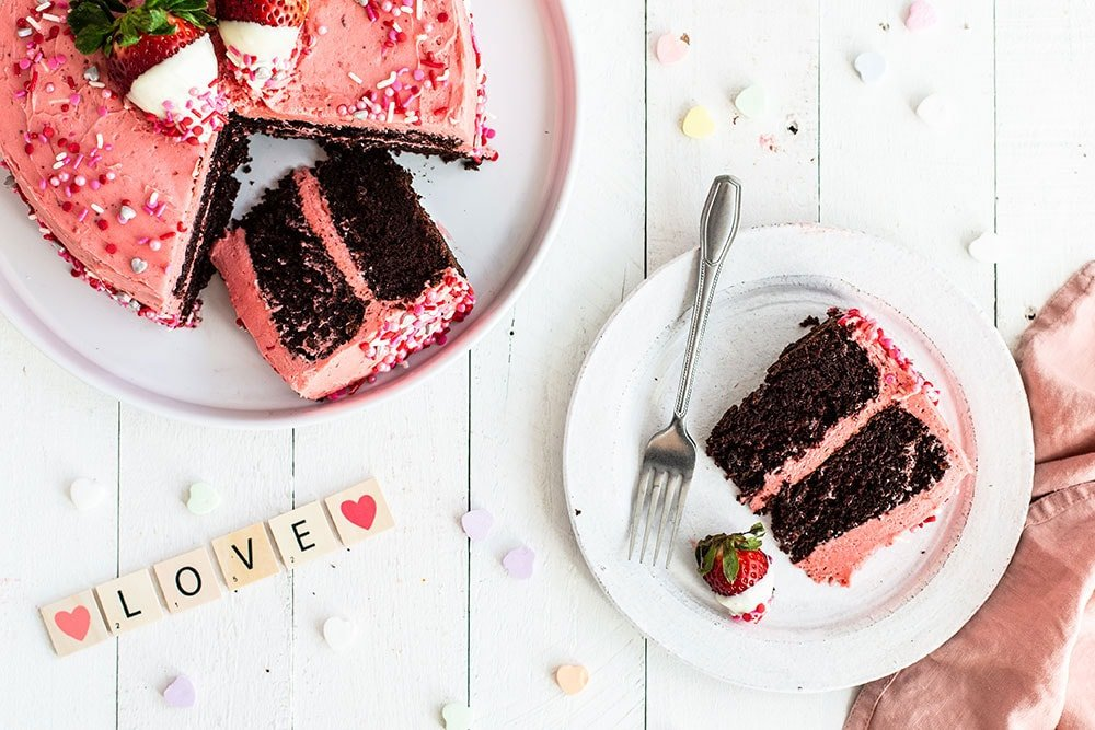 Slice of chocolate and strawberry Valentine's Day cake on a plate with the whole cake and conversation hearts on the table