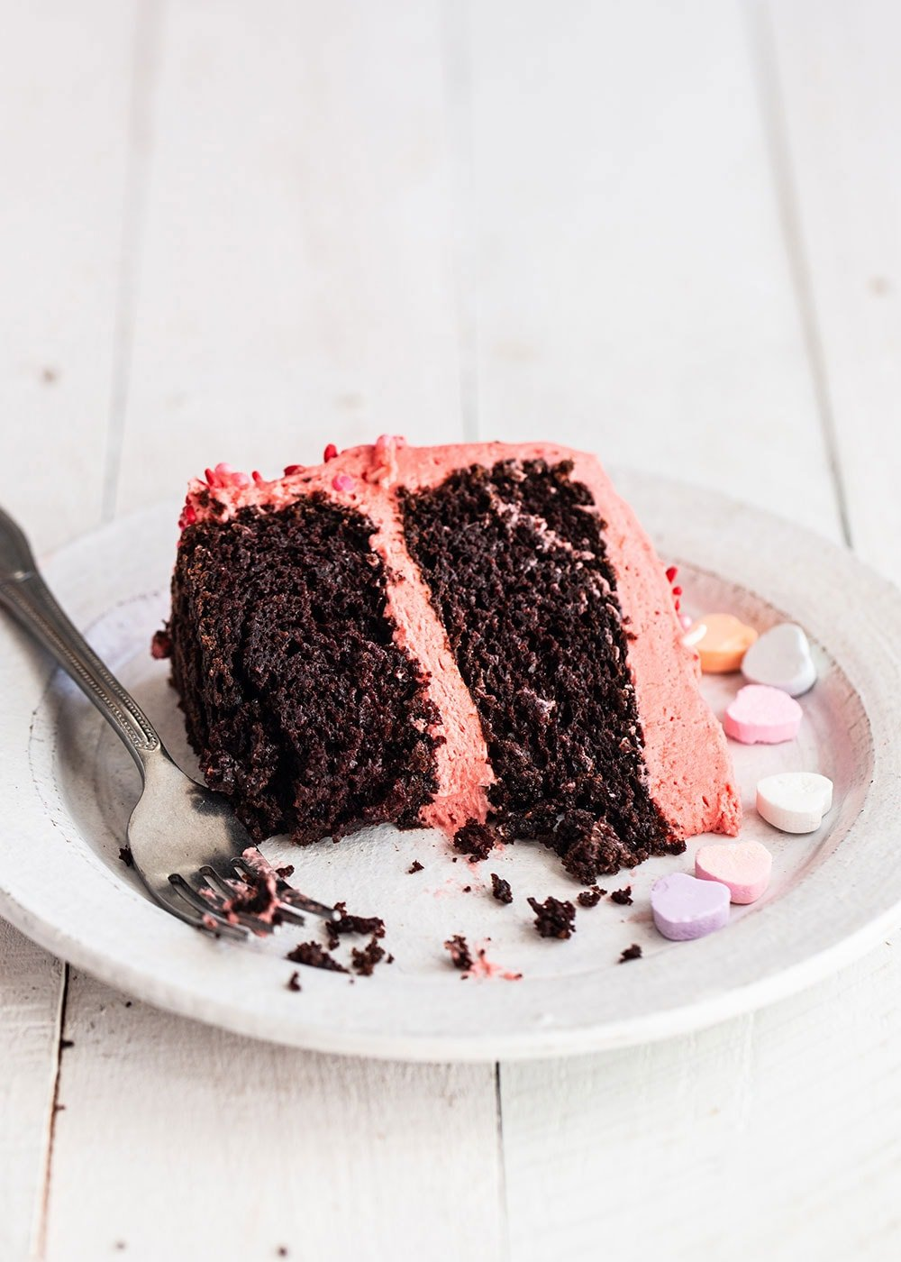 Slice of chocolate cake with strawberry frosting on a plate with Valentine Conversation heart candies