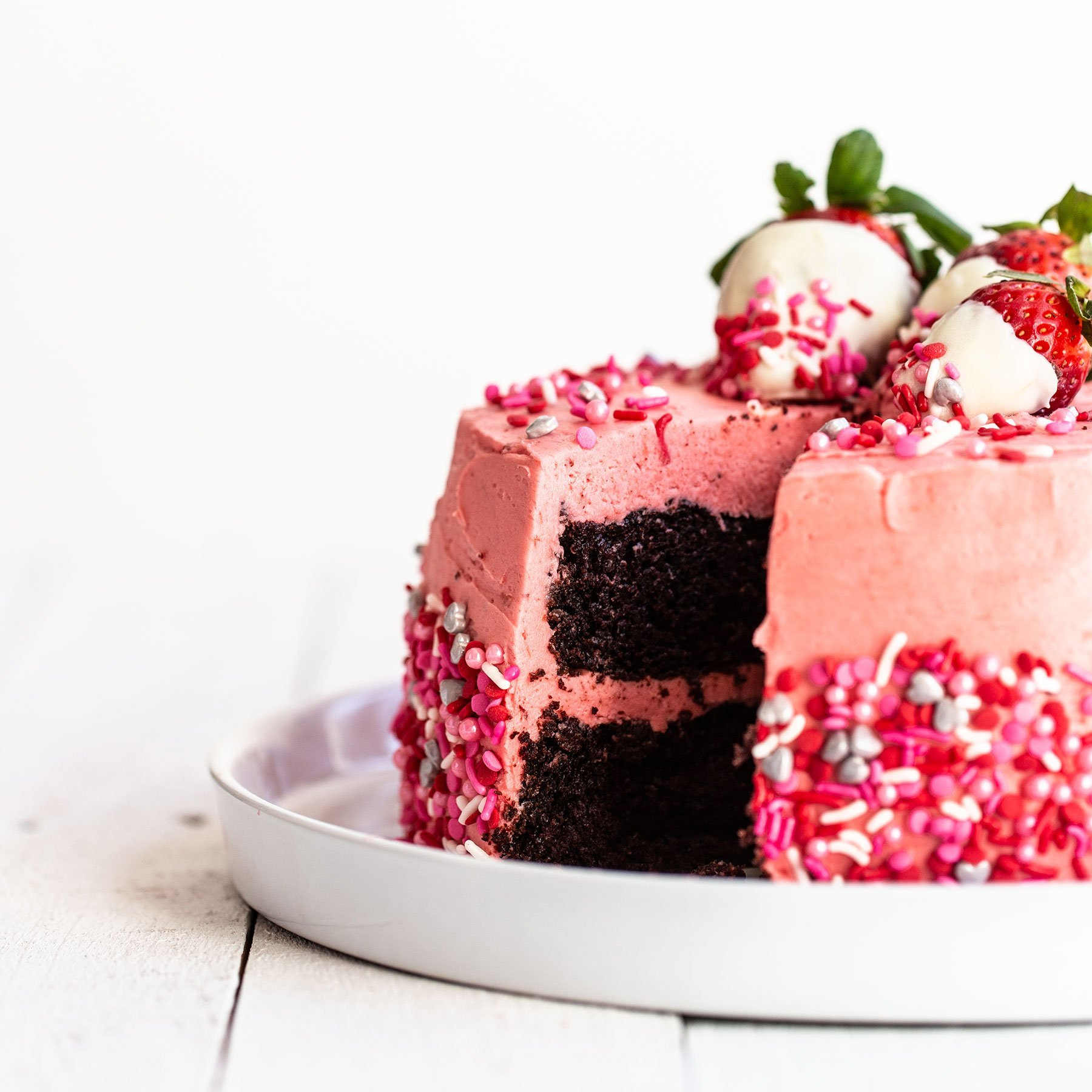 Valentine's Day cake on a cake plate with chocolate covered strawberries on top