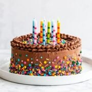 Cake on platter with sprinkles and candles