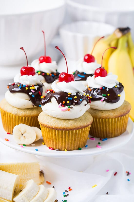 Banana cupcakes with vanilla buttercream frosting, chocolate ganache, sprinkles, whipped cream, and a cherry on top.