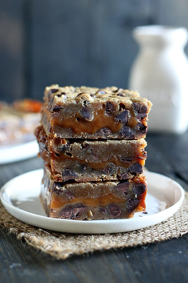 Salted Caramel Cookie Bars feature two layers of chocolate chip cookie sandwiching a thick layer of EASY salted caramel for the perfect salty sweet treat. No mixer required!
