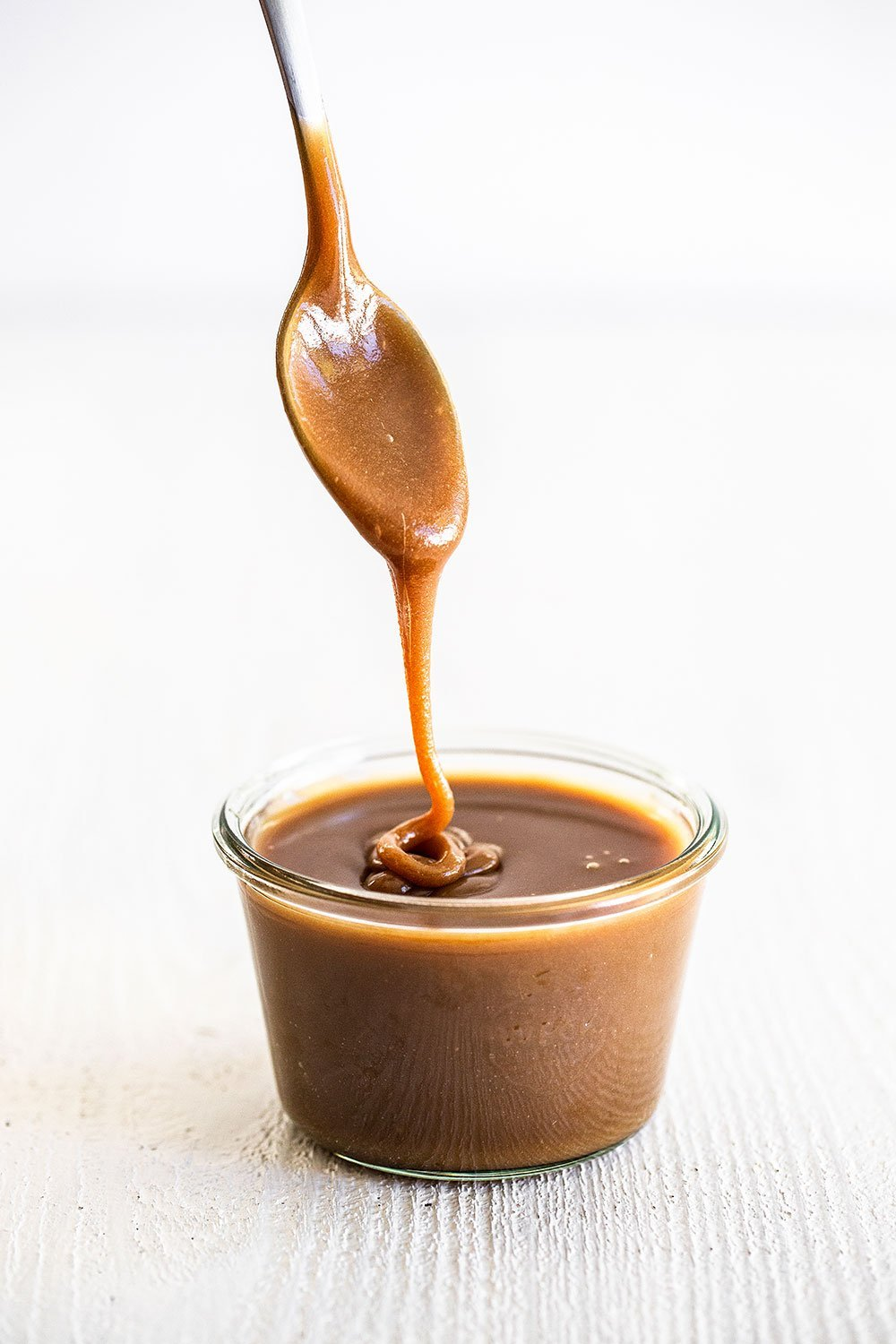 Butterscotch sauce in a jar with a spoon