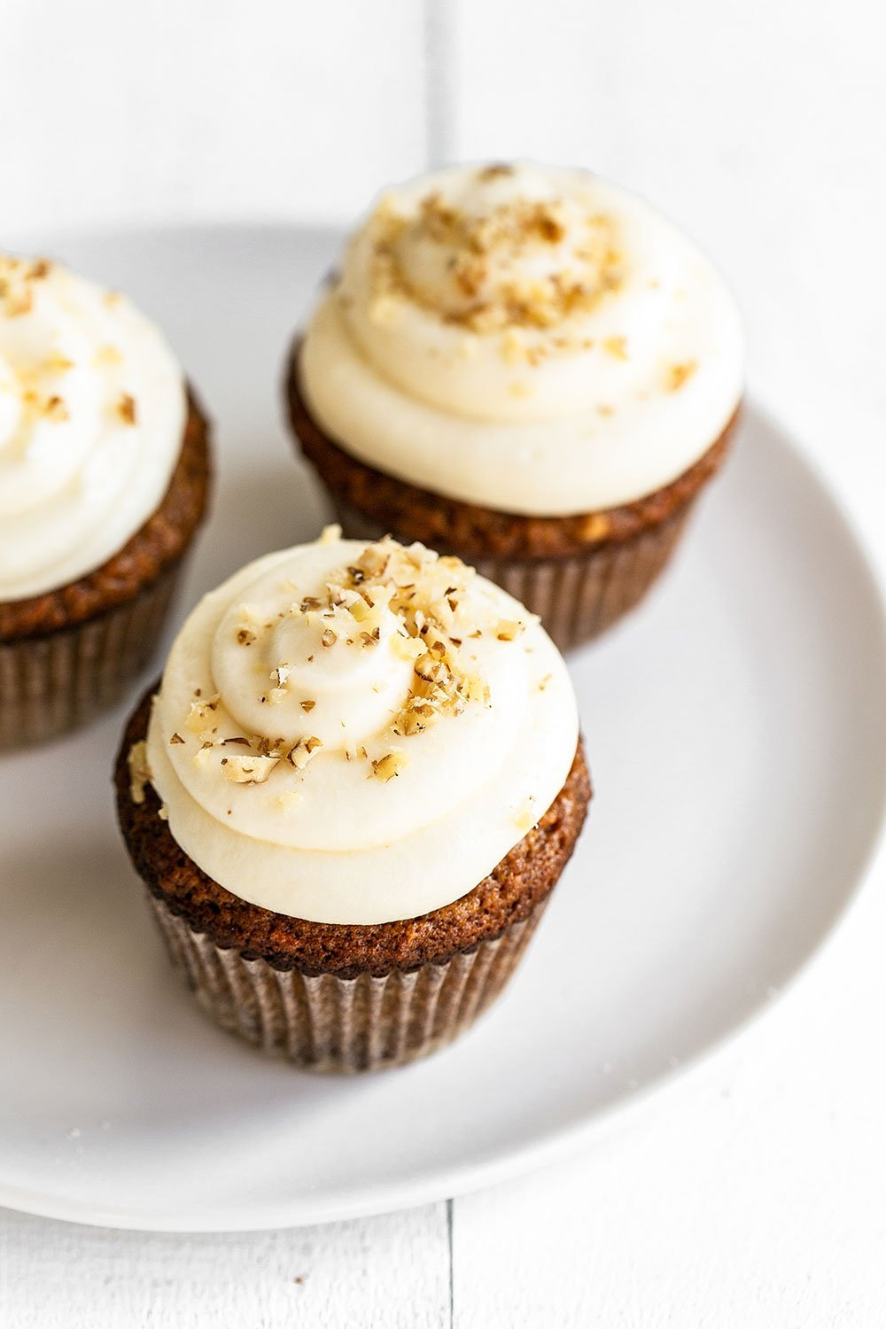 Carrot cupcakes on a plate garnished with chopped walnuts