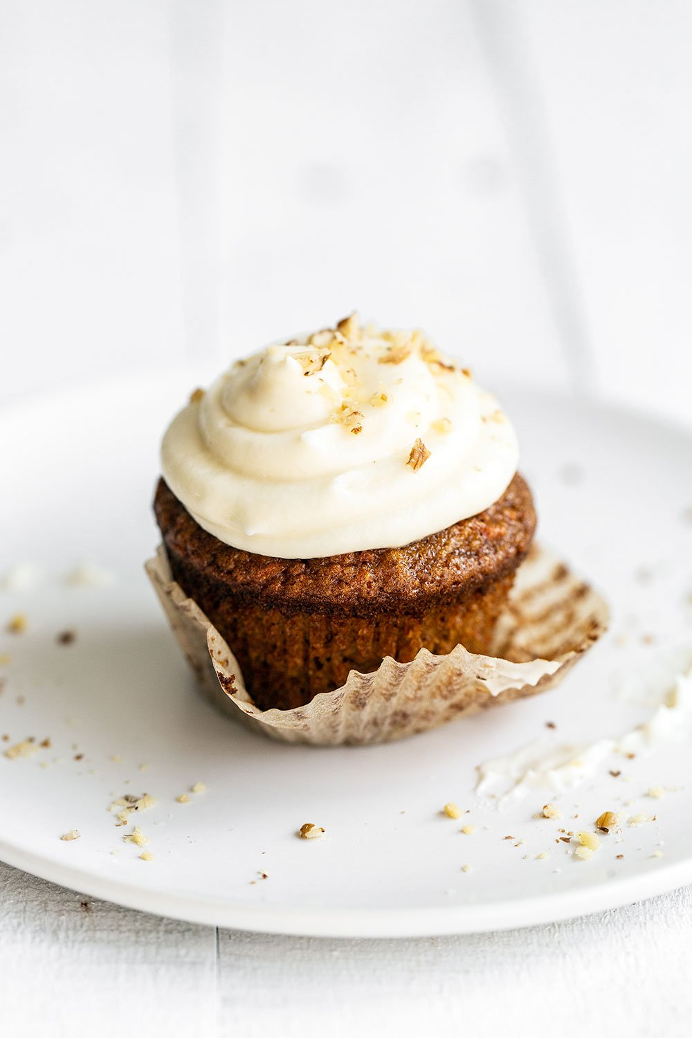 Carrot cupcake on a plate with wrapper being removed