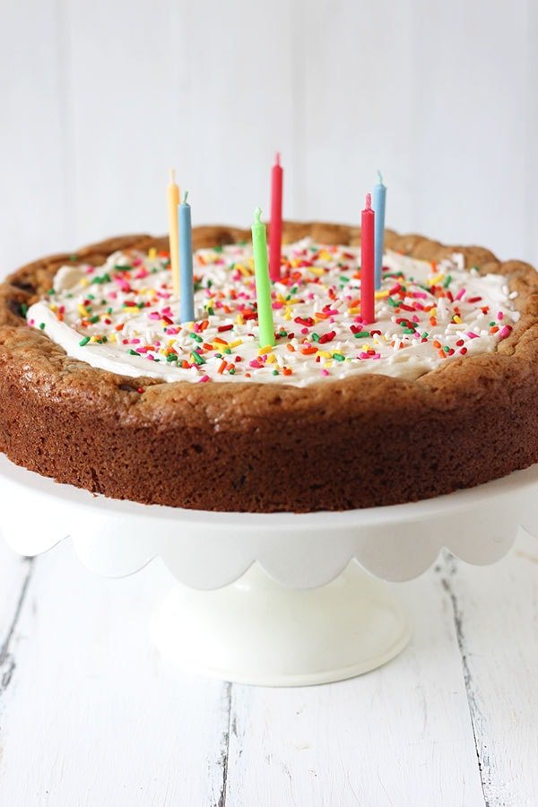 This Chocolate Chip Cookie Cake recipe features a thick base of chewy and slightly gooey chocolate chip cookie topped with creamy vanilla buttercream and garnished with ALL the sprinkles. It's the perfect birthday cake for any cookie lover!