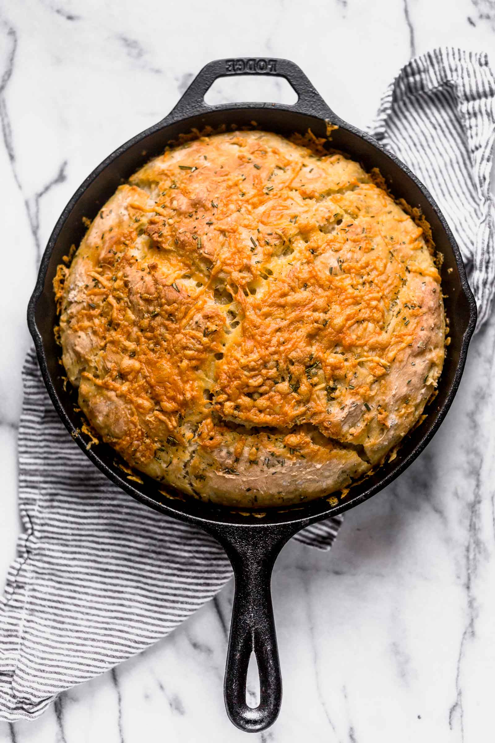 No Knead Rosemary Parmesan Skillet Bread features a super easy homemade dough that comes together in a matter of minutes! This bread has tons of flavor and a crispy cheesy crust.