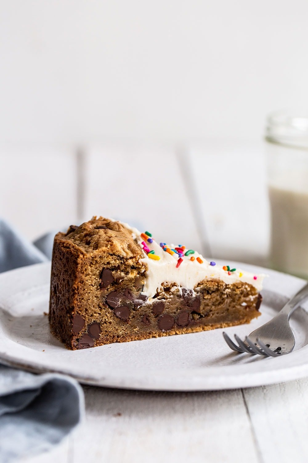 Slice of chewy and gooey chocolate chip cookie cake with vanilla frosting on top