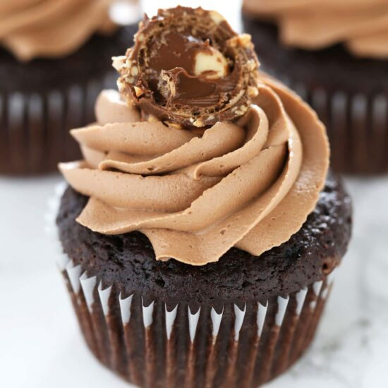 NUTELLA OVERDOSE!!! Ultimate Nutella Cupcakes feature my perfectly moist chocolate cupcake base which is filled with Nutella, topped with Nutella buttercream, and garnished with a Ferrero Rocher candy! It's Nutella perfection!