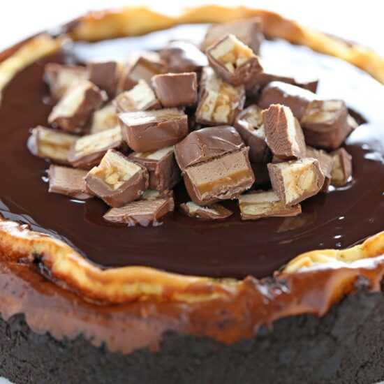 YES! This is PERFECT! Leftover Halloween Candy Cheesecake using up ALL those Snickers, Twix, Reese's, Milkyway taking up space in your pantry in one over-the-top cheesecake recipe!