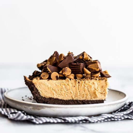 Slice of scratch made Peanut Butter Pie on a plate topped with mini Reese's, peanut butter chips, melted chocolate and peanut butter