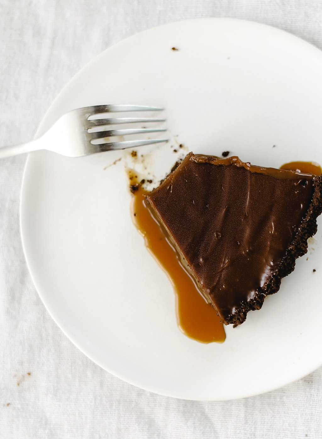 Nutella Caramel Tart features a chocolate graham cracker crust, a layer of hidden homemade salted caramel, and a rich Nutella fudge filling. Pure bliss!