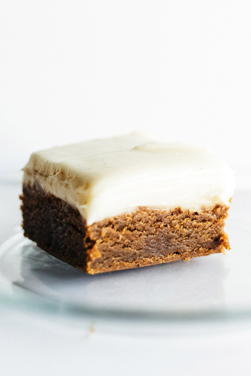 slice of homemade gingerbread cookie bar on a glass plate with cream cheese frosting on top