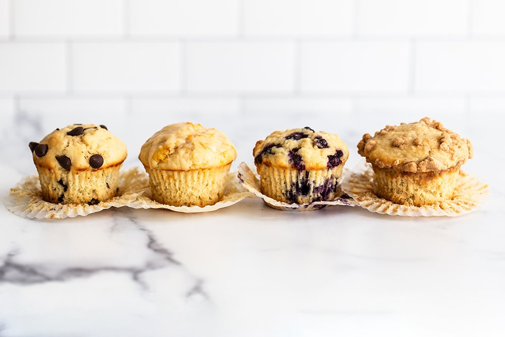chocolate chip, lemon, blueberry and coffee cake muffins on a marble board