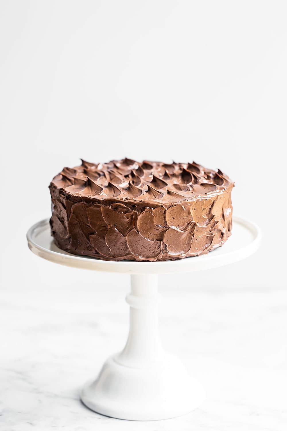Best Chocolate Cake with Swiss Meringue Buttercream on a cake stand