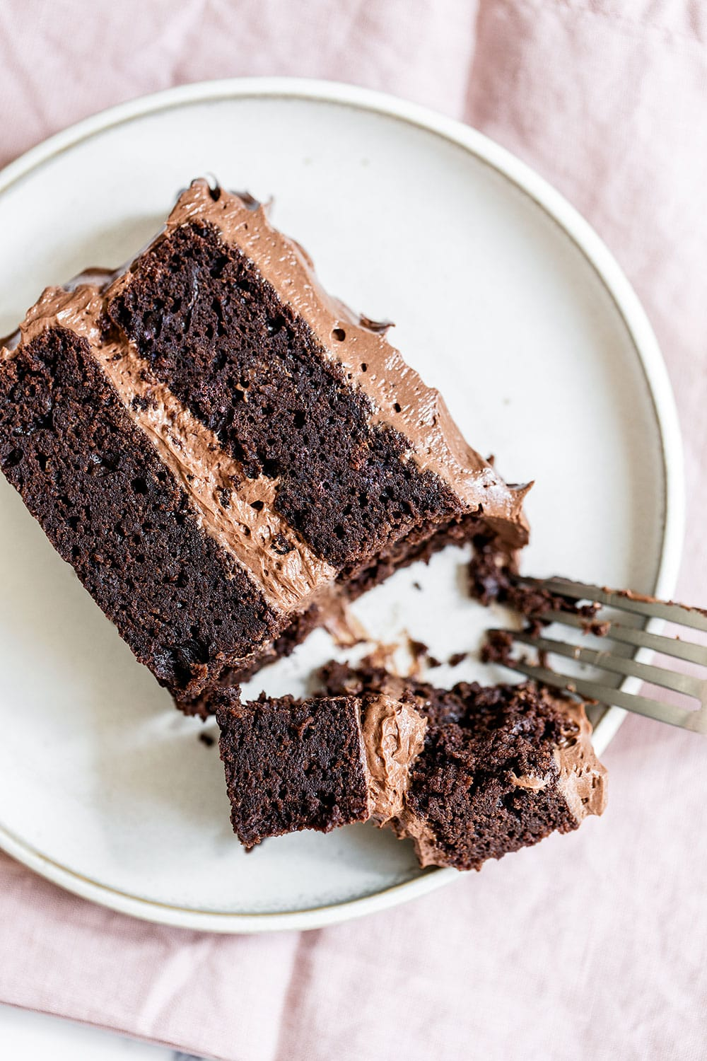 Rich slice of the best chocolate cake recipe with a fork taking a bite